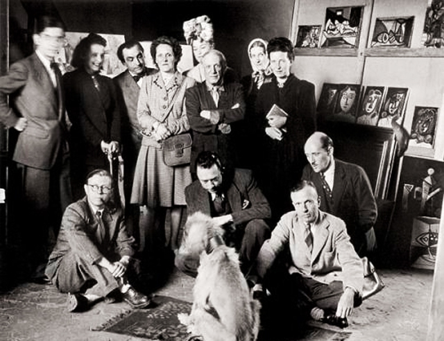 Sartre (seated front left) next to Camus, with Picasso's dog, and artists and intellectuals including Picasso, de Beauvoir and Eluard, 1944.